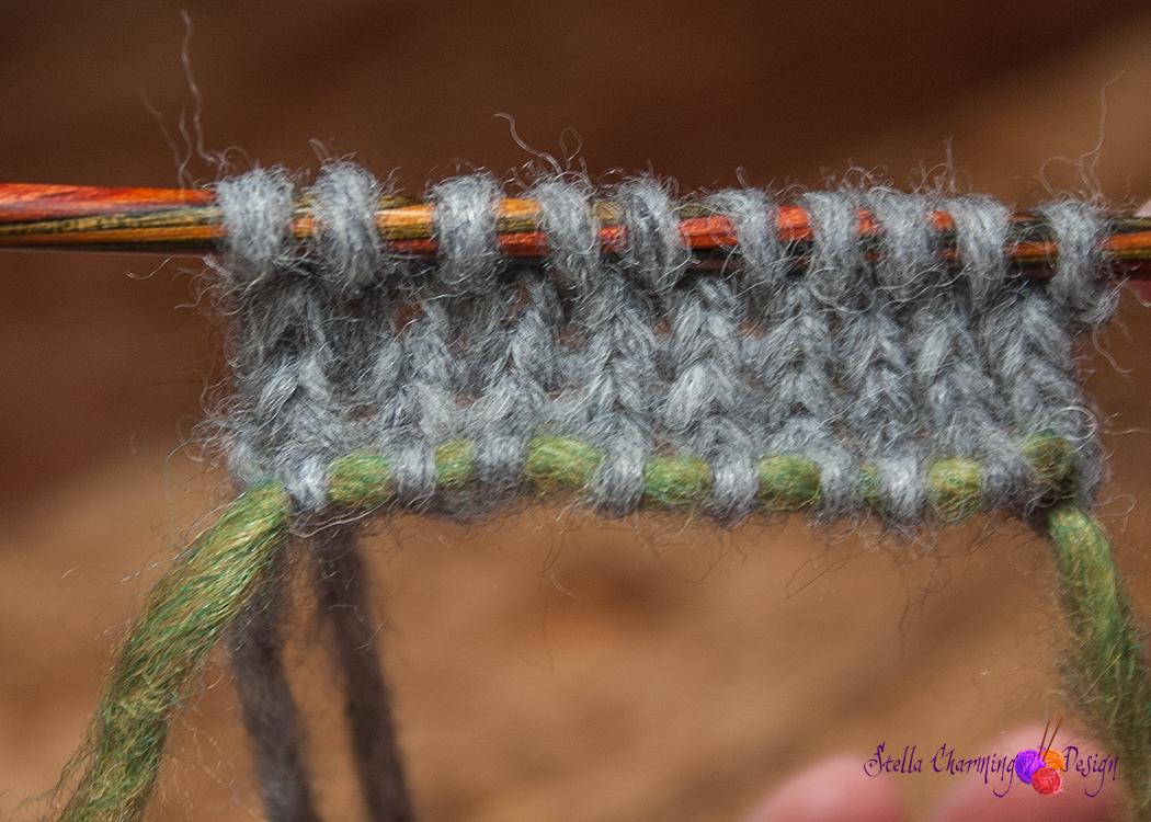 Slik ser det ut når du har strikket noen pinner. Hjelpetråden holder maskene fra opplegget på vent.